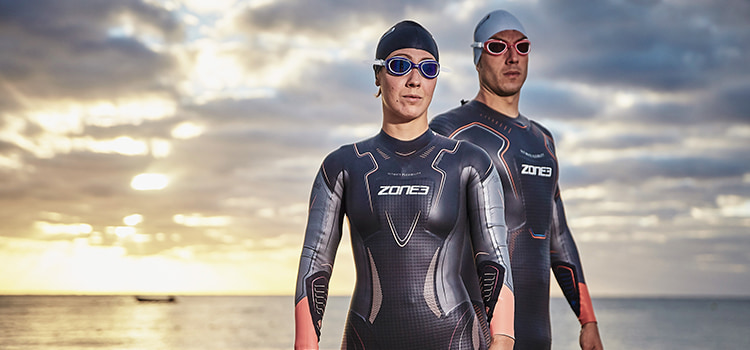 Guy and girl stood by sea in zone3 wetsuit, hat a goggles