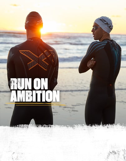 Two people stood by the sea in their 2XU wetsuits