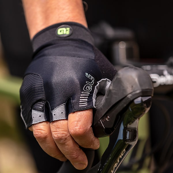Close up of someone wearing a black Ale fingerless cycle glove