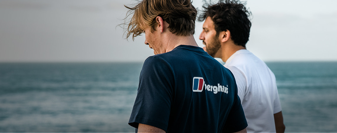 Two guys walking by the sea wearing Berghaus t-shirts