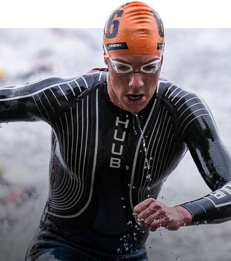 Person coming out of water from event wearing a Huub wetsuit