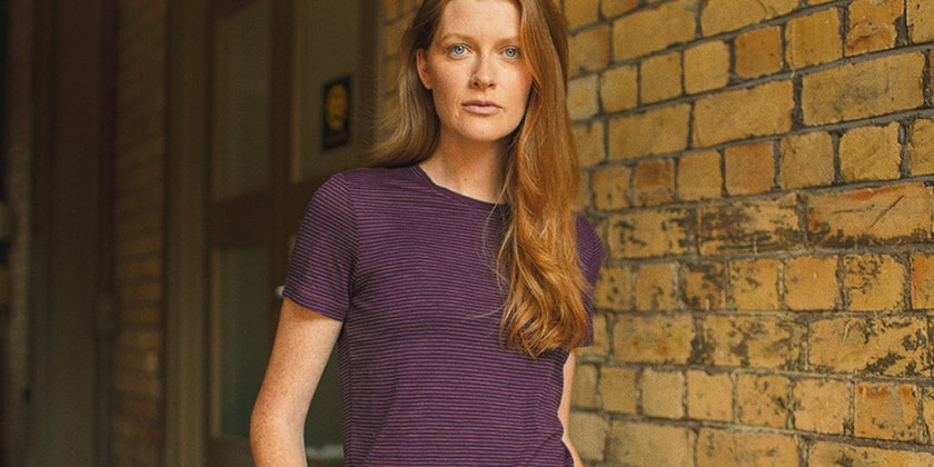 Girl wearing a purple and black stripey Icebreaker top