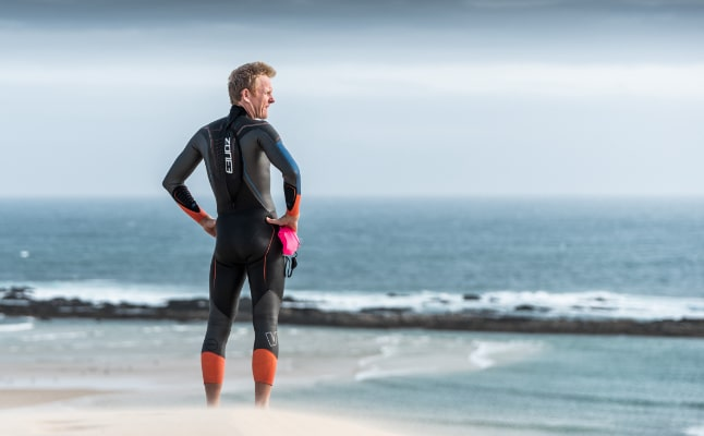 Guy stood by the sea in a Zone3 wetsuit, about to go for an open water swim