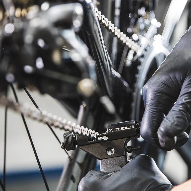 A close up of a person wearing black protectcive gloves using X-Tools to clean and maintain their bike.